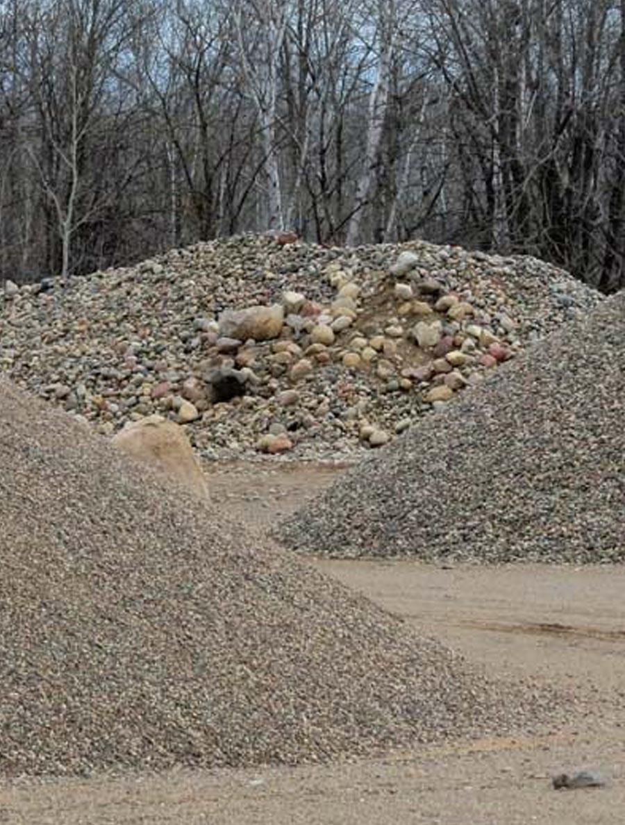 A dump truck dumping gravel on excavation site.   Vertical.